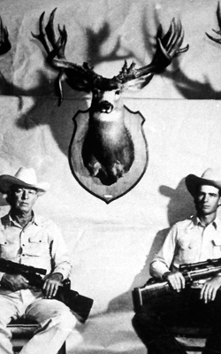 Old picture of two hunters in front of their prized stuffed stag.