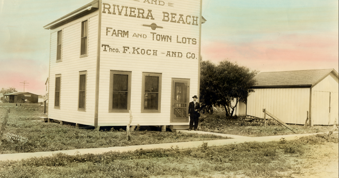 A man standing in front of the Riviara Beach Farm and Town Lots building.